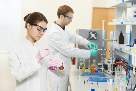 Two chemist researchers workers in laboratory photo