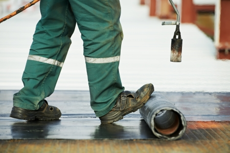 dach: Roofer Installation Dachpappe mit Erhitzen und Schmelzen von Bitumen Rolle von Fackel Flamme während Dachreparatur
