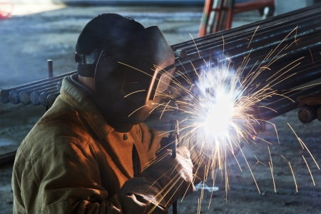 welding metal: welder worker welding metal by electrode with bright electric arc and sparks during manufacture of metal equipment Stock Photo