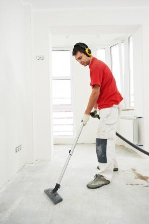 artesano: trabajador limpieza de suelos en rehabilitación de viviendas Foto de archivo