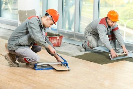alba�il: Dos soladores de renovaci�n industrial piso de baldosas Foto de archivo