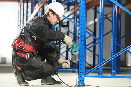 an erection: warehouse worker installing rack arrangement Stock Photo