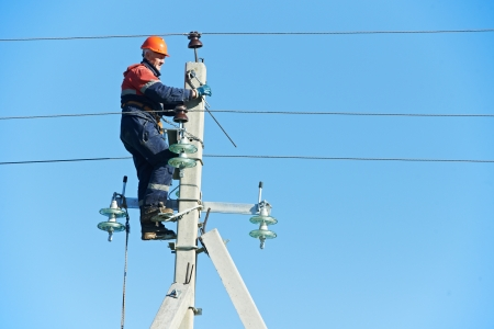 high voltage: power electrician lineman at work on pole