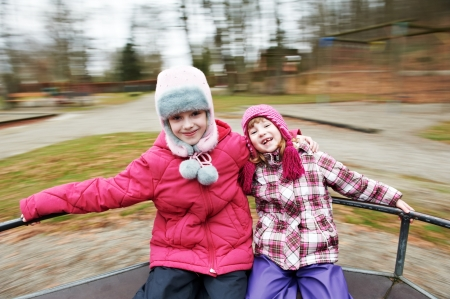 carrousel: two little laughing kids girls on carrousel Stock Photo
