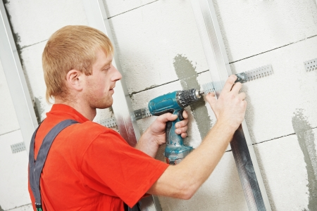 plasterboard: carpenter with plasterboard and screwdriver