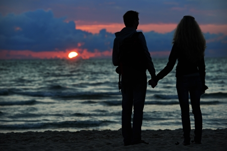 Young family couple at sunset beach photo