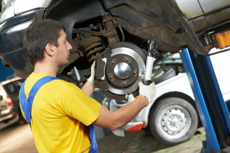 auto mechanic at car suspension repair work photo