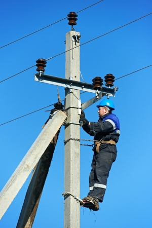 power distribution: power electrician lineman at work on pole