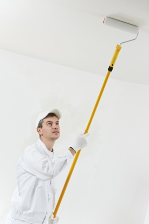 priming paint: house painter at work with painting roller Stock Photo