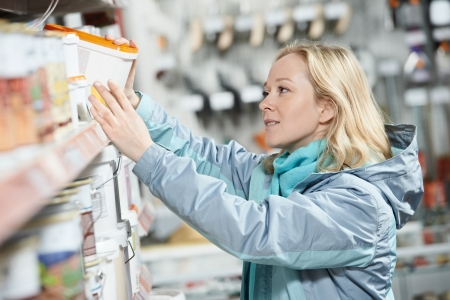 買い物のハードウェア店でペンキの女性 写真素材