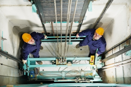 maintenance engineer: machinists adjusting lift in elevator hoist way