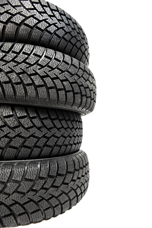 tire fitting: Stack of four car wheel winter tyres isolated