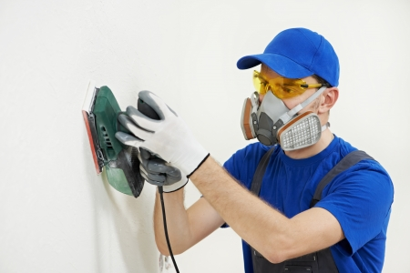 respirator: worker with orbital sander at wall filling