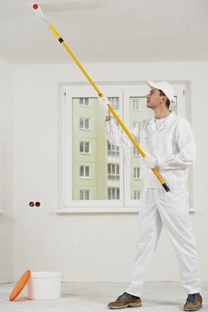 pintor de casas: casa pintor en el trabajo con el rodillo pintura Foto de archivo