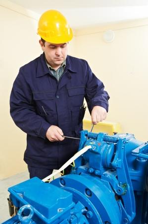 machinist: Machinist tuning elevator brakes mechanism Stock Photo