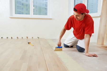 lying on the floor: parquet worker adding glue on floor Stock Photo