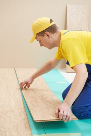 tongue and groove: cork worker at flooring work Stock Photo