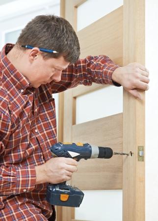 door man: carpenter at door lock installation Stock Photo