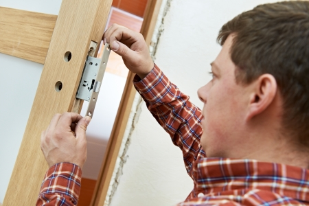 carpenter at door lock installation photo