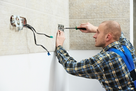 Electrician installing wall outlets photo