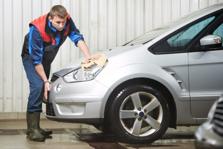 worker cleaning car with water and sponge photo