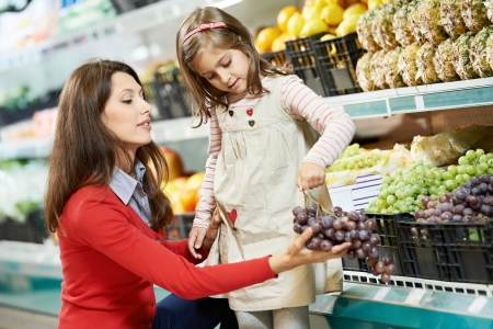 mother and girl shopping in supermarket photo