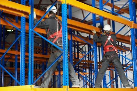 rack arrangement: two warehouse workers installing rack arrangement