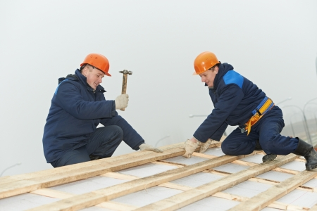 roofing workers hammer roof boarding photo