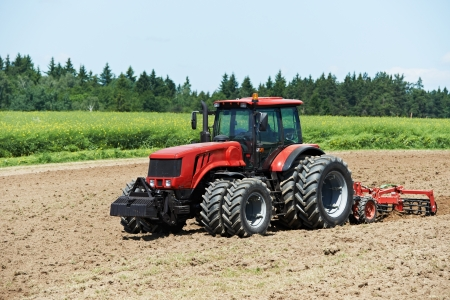 agronomy: Ploughing tractor at field cultivation work