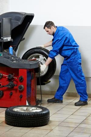 balancing: repairman mechanic at wheel balancing