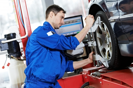 automobile workshop: auto mechanic at wheel alignment work with spanner
