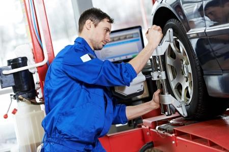 mecanico automotriz: mecánico de automóviles en el trabajo de alineación de ruedas con una llave
