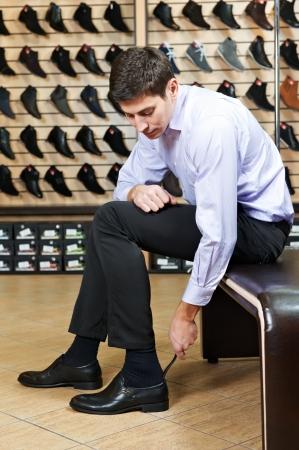 comprando zapatos: Hombre joven que intenta en los zapatos Foto de archivo