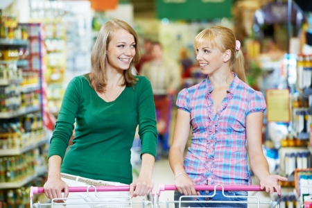 two women at supermarket shopping photo