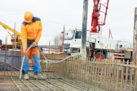 builder worker vibrating concrete in form Stock Photo - 17411826