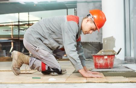 tiler at industrial floor tiling renovation work photo
