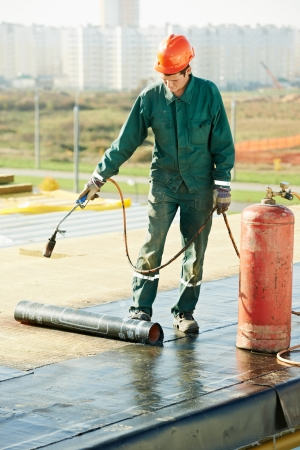 roofing system: Flat roof covering repair works with roofing felt Stock Photo