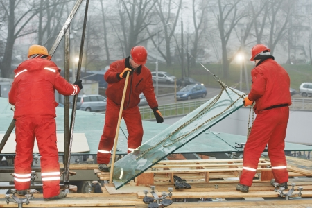 erector: workers installing glass window on building