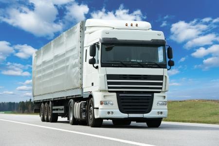 푸른 하늘에 회색 트레일러와 함께 흰색 트럭 스톡 콘텐츠