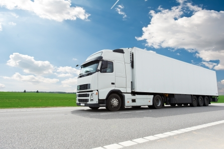 truck on highway: white lorry with trailer over blue sky Stock Photo