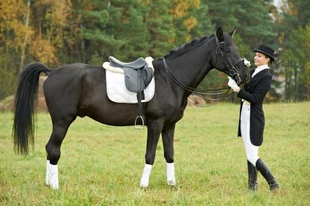 mujer en caballo: mujer jinete con el caballo en uniforme Foto de archivo