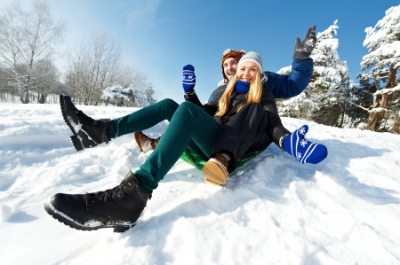man resting: young happy couple sledding in winter