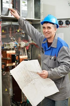 solucion de problemas: Electricista feliz trabajando en la caja de la línea de alimentación Foto de archivo