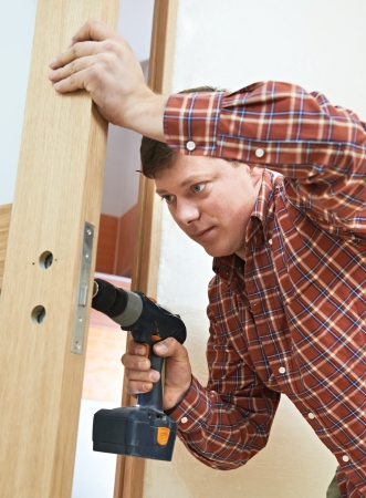 deadbolt: carpenter at door lock installation Stock Photo