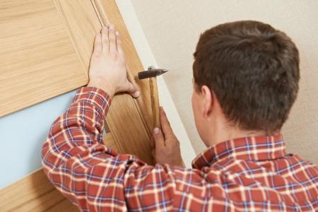door casing: carpenter at door lock installation Stock Photo