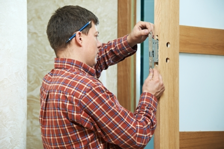 manual job: carpenter at door lock installation Stock Photo