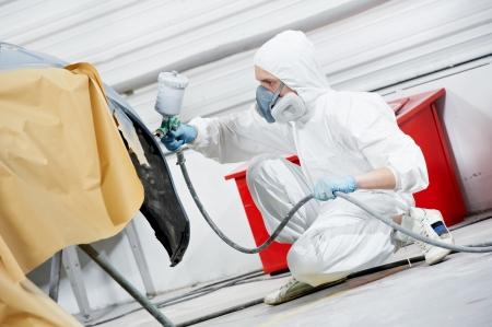 automotive industry: auto mechanic painting car bumper
