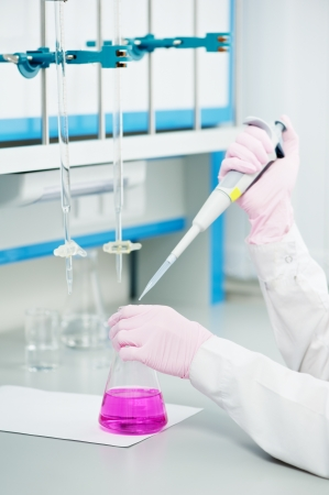 doctor hands with flask dropper in a laboratory photo