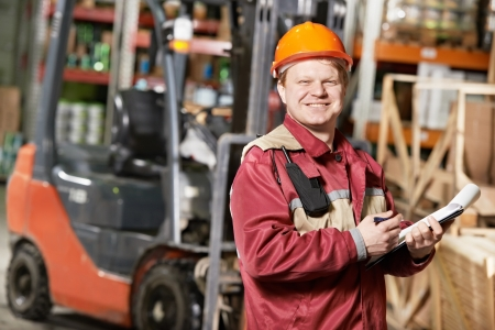 warehouse worker in front of forklift photo
