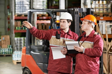 moving crate: warehouse workers in front of forklift